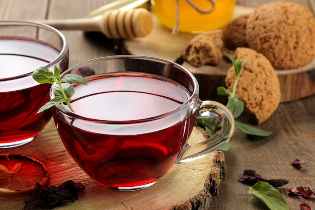 Hot red karkade tea with honey and mint. autumn or winter soft drink. on a brown wooden table.