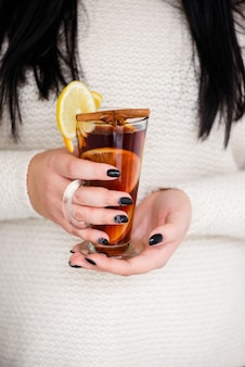 Hot red mulled wine in man hands.