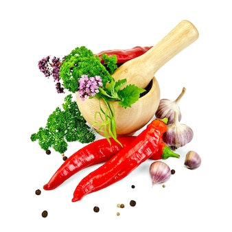 Hot red pepper, garlic, parsley, peppercorns and mustard, mint, tarragon, marjoram in wooden mortar isolated on white background