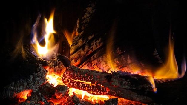 Горячий ревущий огонь и красные угли в камине горящие дрова в дымоходе и тепло атмосферы