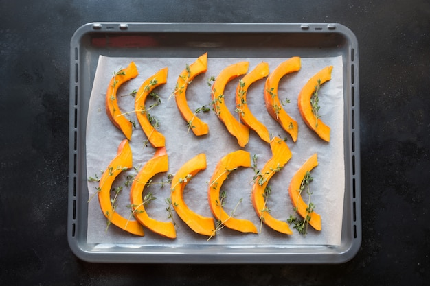 Горячая жареная нарезанная тыква с тимьяном, оливковым маслом и солью на противень. вкусная закуска. шаблон питания.