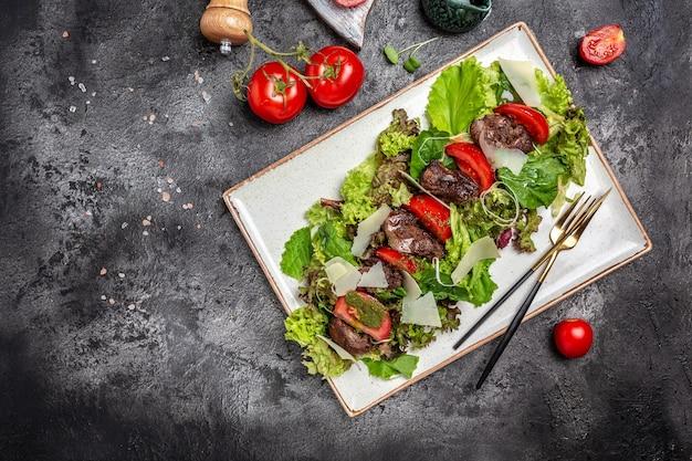 접시에 닭 간, 버섯, 샐러드 잎, 파마산 치즈, 체리 토마토를 곁들인 뜨거운 샐러드. 건강 식품, 배너, 메뉴, 텍스트를 위한 요리법 장소, 상위 뷰
