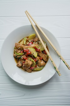 Hot salad with chicken, zucchini and chili pepper, sprinkled with sesame seeds and herbs. asian food. white wood .