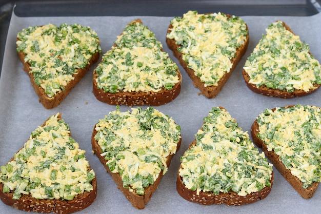 Горячие бутерброды с диким чесноком, зеленым луком, яйцами, сыром и петрушкой, расположенные на пергаментной бумаге на противне на белом фоне, вид сверху