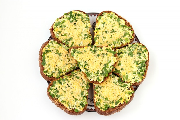 Hot sandwiches with wild garlic, green onions, eggs, cheese and parsley located on white background