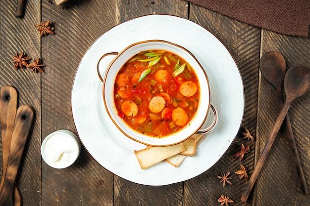 Горячий колбасно-томатный суп в белой миске на деревянном столе