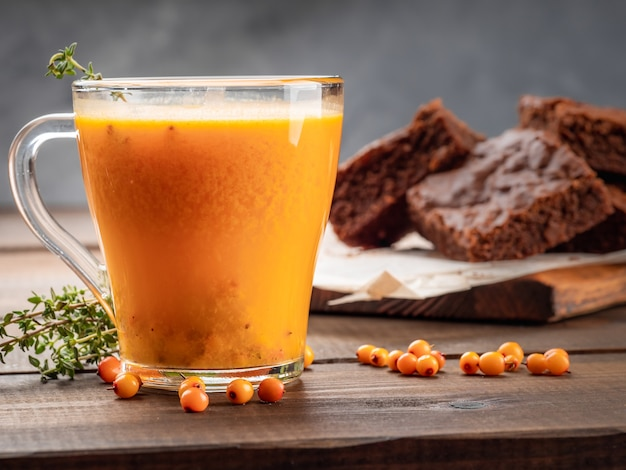 Горячий напиток из облепихи с тимьяном стоит на деревянном столе с пирожным.