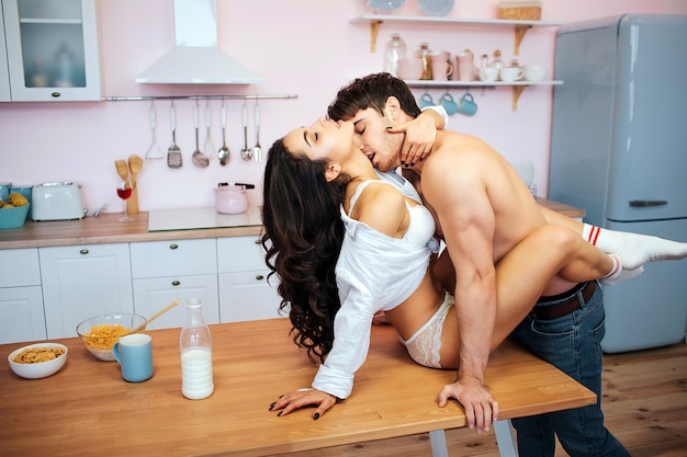 Hot sexy couple having intercourse on table. young woman sit there and enjoy.