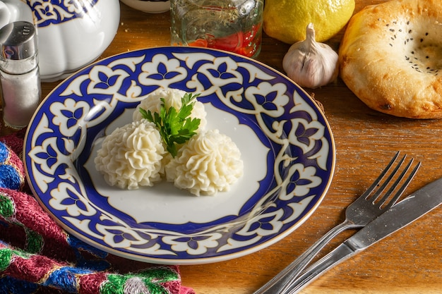 Hot side dish of mashed potatoes in the shape of a flower decorated with parsley in a plate with a traditional uzbek pattern