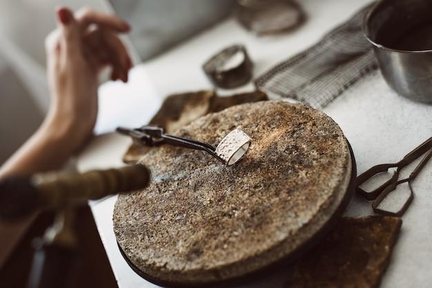 뜨거운 은색. 납땜 후 보석상 작업대에 있는 뜨거운 은색 반지를 닫습니다. 보석상 작업대. 보석류. 사업. 보석 작업실. 보석 제조