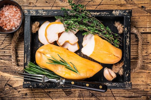 허브와 함께 나무 보드에 뜨거운 훈제 닭 가슴살 등심 고기. 나무 테이블. 평면도.