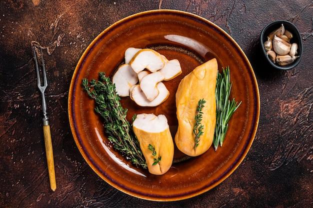 허브와 함께 소박한 접시에 뜨거운 훈제 닭 가슴살 가금류 고기. 어두운 테이블. 평면도.