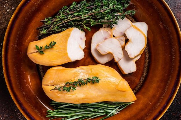 허브와 함께 소박한 접시에 뜨거운 훈제 닭 가슴살 가금류 고기