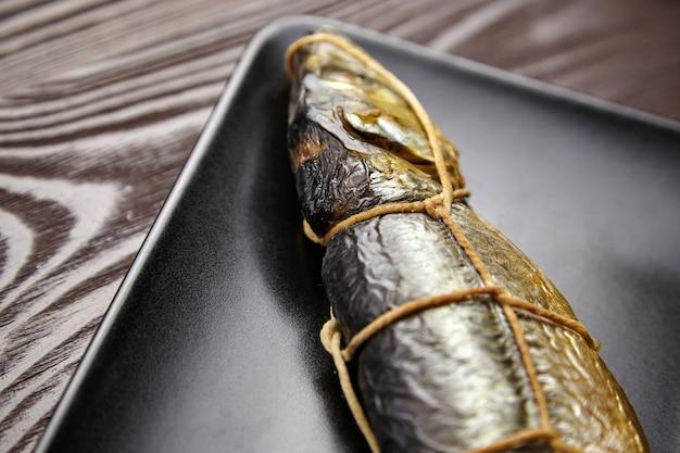 Рыба горячего копчения, сельдь в кипарисе. связанная шпагатом рыба на черной тарелке на коричневом деревянном столе, крупным планом