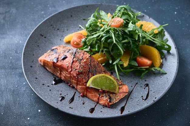 Hot smoked salmon with arugula salad, cherry tomato, and orange