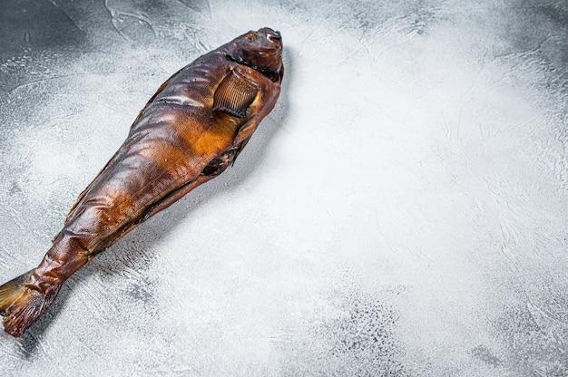 Рыба горячего копчения целая на кухонном столе. белый фон. вид сверху. скопируйте пространство.