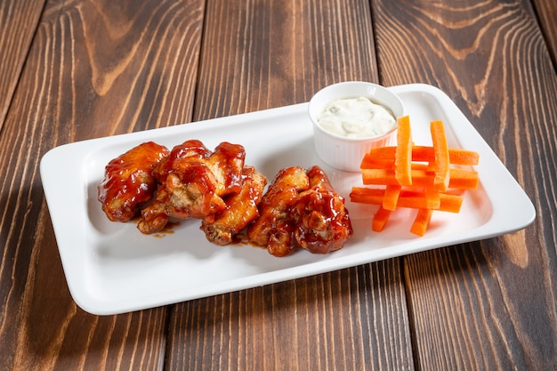 Hot snack with chicken wings barbeque, carrot and white sauce on wooden table