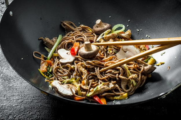 Hot soba noodles in a wok pan with mushrooms, sauce and beef. on black rustic background