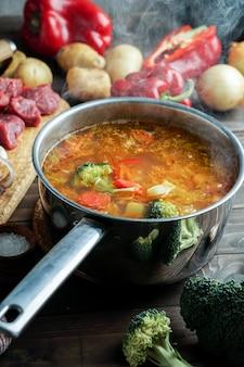 Дымится горячий суп в кастрюле. с говядиной и овощами. сытное, питательное блюдо. ужин