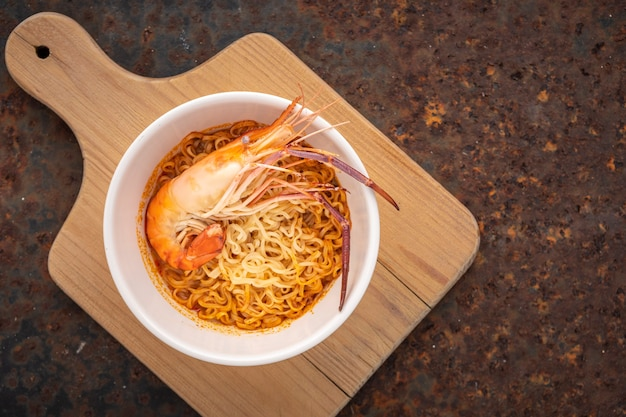 Hot and sour noodle soup with shrimp in white ceramic bowl on wooden cutting board, top view, river prawn, tom yum goong, tom yum kung, thai food