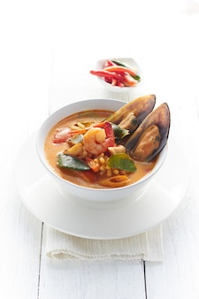 Hot and sour seafood soup on white.