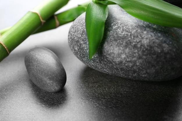 Горячие спа-камни с бамбуком на сером столе, крупным планом