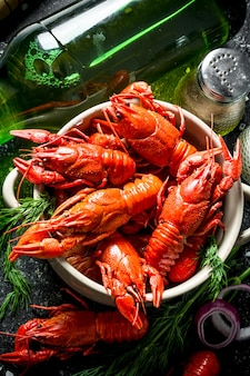 Hot spicy boiled crayfish with a bottle of beer and spices on black rustic table