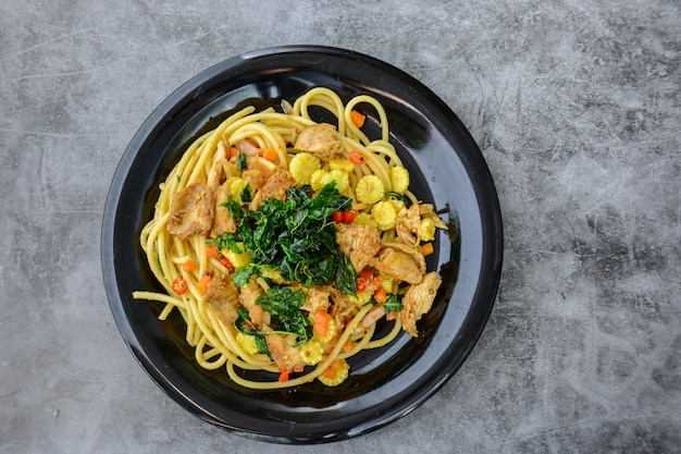 Hot and spicy chicken spaghetti, topping with crispy sweet basil and sliced baby corn