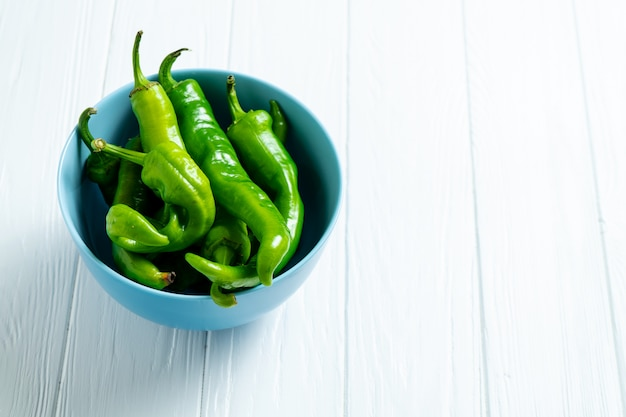 Hot, spicy green peppers in a blue bowl on a white wooden background with copy space.