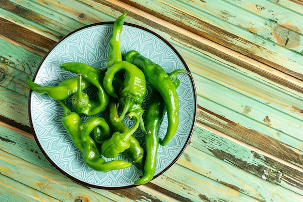 Hot, spicy green peppers in a blue bowl on a wooden background