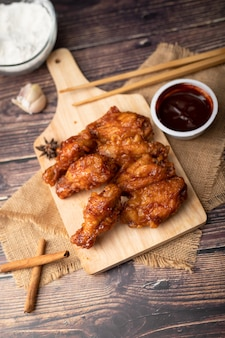 Hot and spicy korean barbeque fried chicken on wood cutting board
