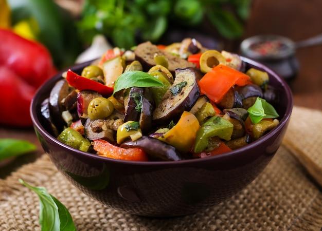 Spezzatino piccante speziato di melanzane, peperoni, olive e capperi con foglie di basilico.