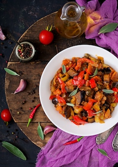 Hot spicy stew eggplant, sweet pepper, tomato and capers. flat lay. top view
