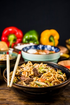 Hot and spicy stir fried instant noodle with beef and vegetable in ceramic bowl