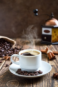 Hot steaming coffee on an old wooden table with coffee beans, manual coffee grinder. vertical view