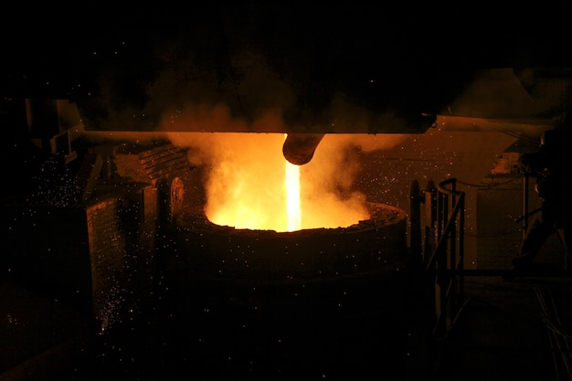 Hot steel pouring in steel plant. molten metal poured from ladle. metallurgical production, heavy industry, engineering, steelmaking.