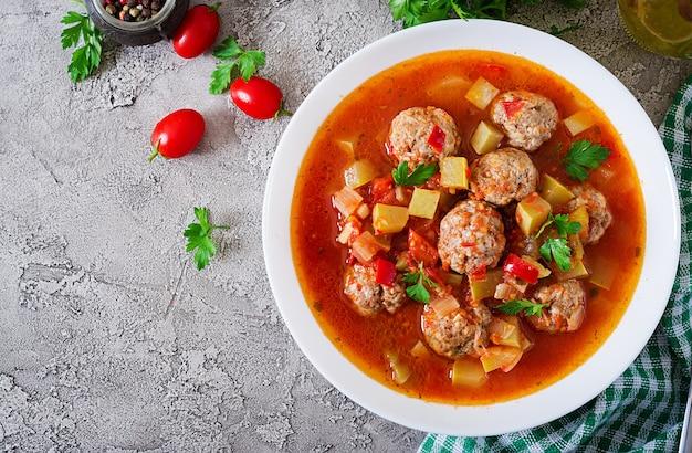 Горячий тушеный томатный суп с фрикадельками и овощи крупным планом в миску на столе. суп из альбондиг, испанской и мексиканской кухни. вид сверху. плоская планировка