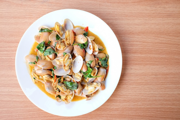The hot stir fried clams with roasted chili paste and basil serve on white dish set on brown table - homemade food concept.