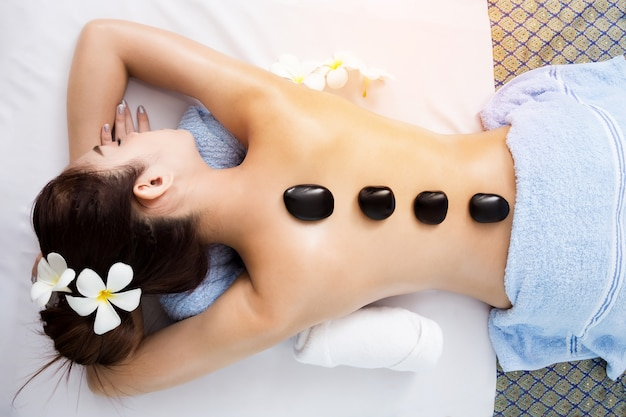 Hot stone on back of asian pretty woman in spa room