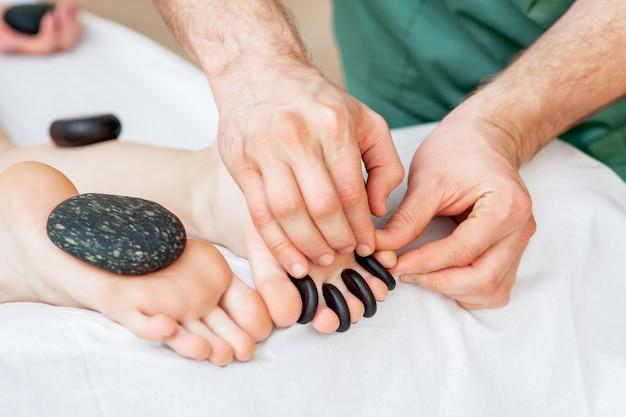 Массаж горячими камнями на пальцах ног.
