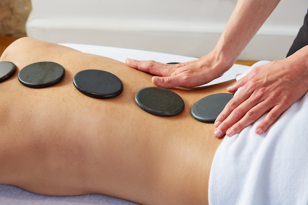 Hot stone massage in woman back physiotherapist