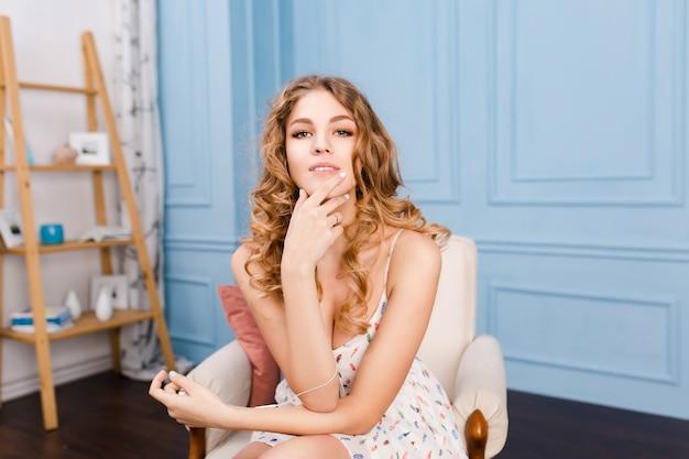 ブロンドの巻き毛を持つホットスタイリッシュな女の子は、青い壁と茶色の家具とスタジオの肘掛け椅子に座っています。
