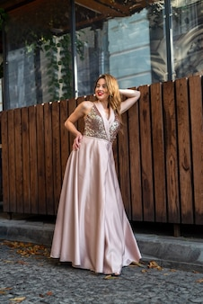Жаркая летняя красавица в модном коктейльном шелковом платье гуляет по городу и наслаждается летним солнечным днем