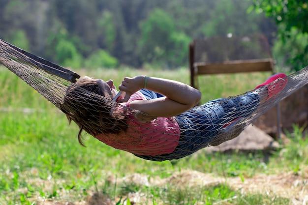 Жаркий летний день, девушка со смартфоном, лежа в гамаке в саду. девушка и гаджет.