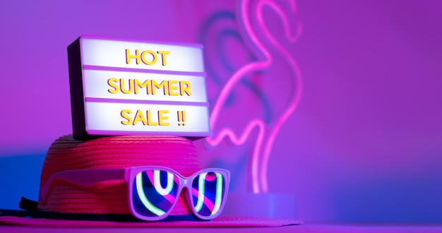 Hot summer sale in light box on hat with sunglasses neon pink and blue and green light on table