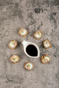 Горячие роллы суши и соевый соус на каменном столе.