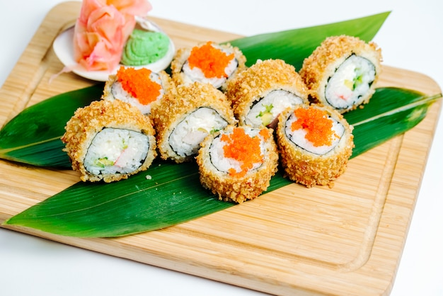 Hot sushi rolls with crab sticks, avocado served on leaves on wood board