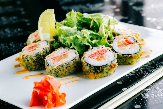 Hot sushi rolls with salmon and ginger garnished with spicy mayonnaise