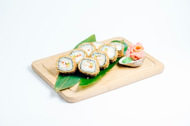Hot sushi rolls with tempura and avocado served on leaves on wood board