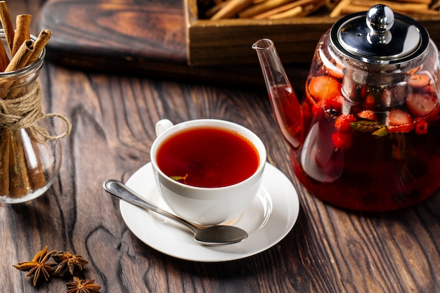 Hot sweet berry tea in white cup and glass teapot